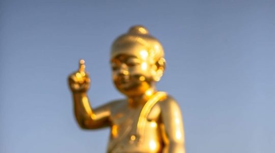 A Buddhist monk praying in front of the baby Buddha statue